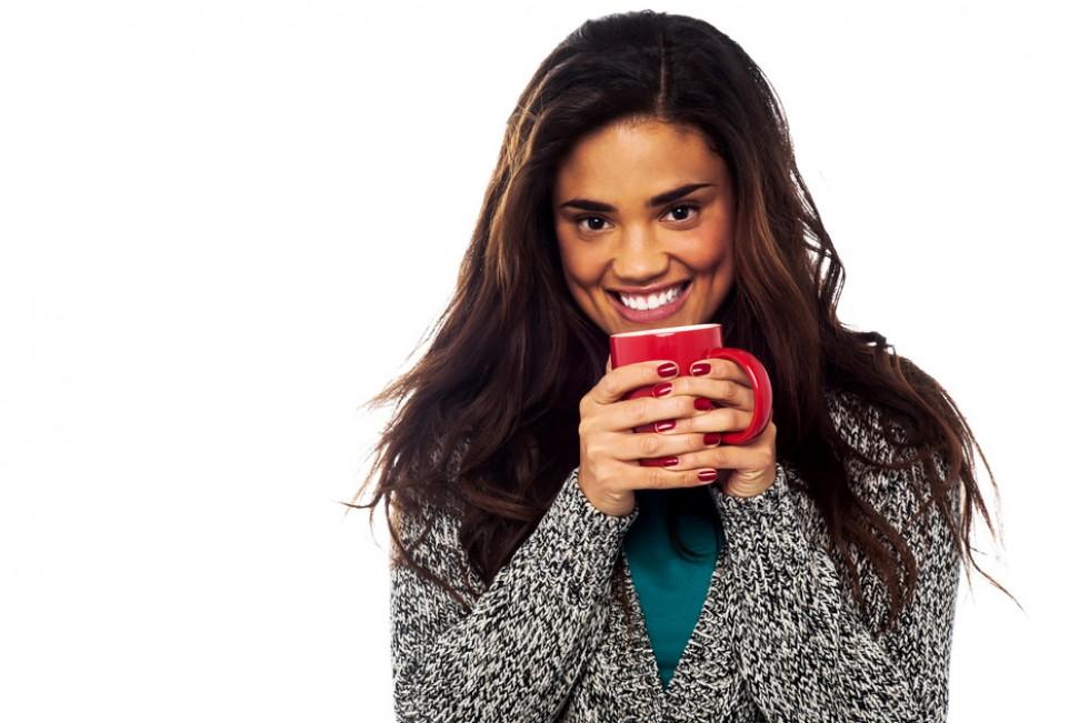 Beautiful african woman drinking coffee or tea.
