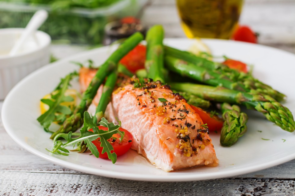 Baked salmon garnished with asparagus and tomatoes with herbs
