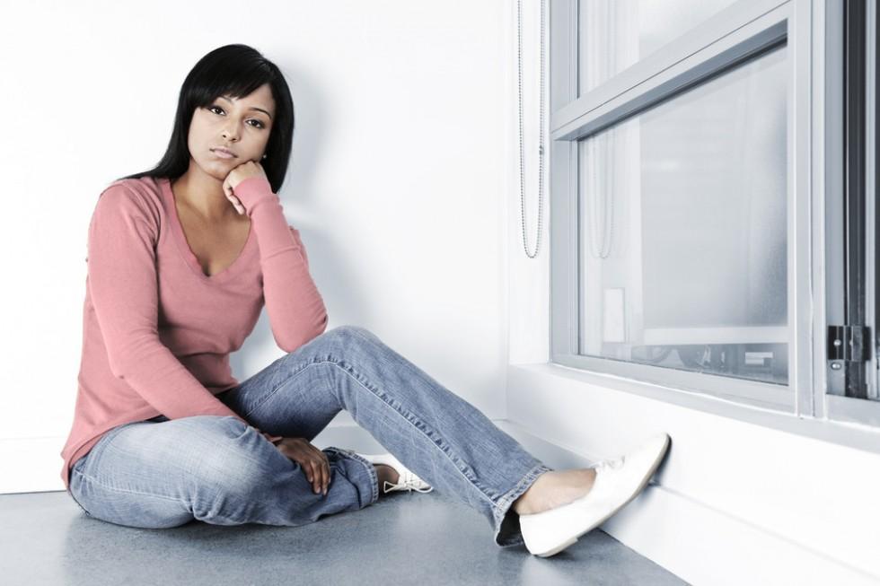Depressed woman sitting on floor