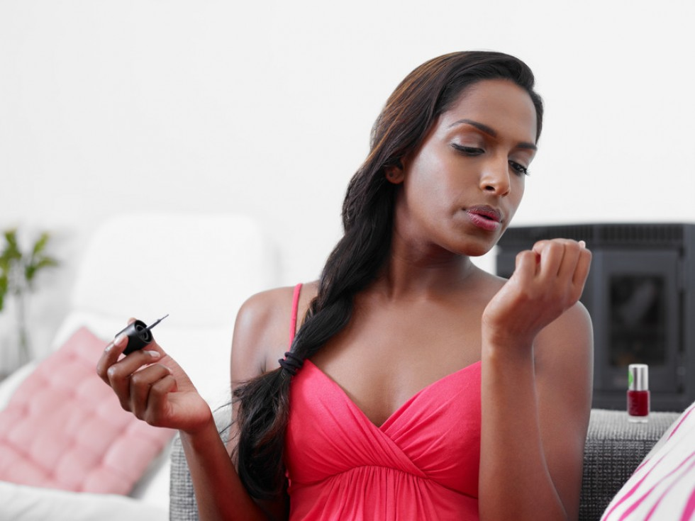 woman applying red nail varnish on sofa