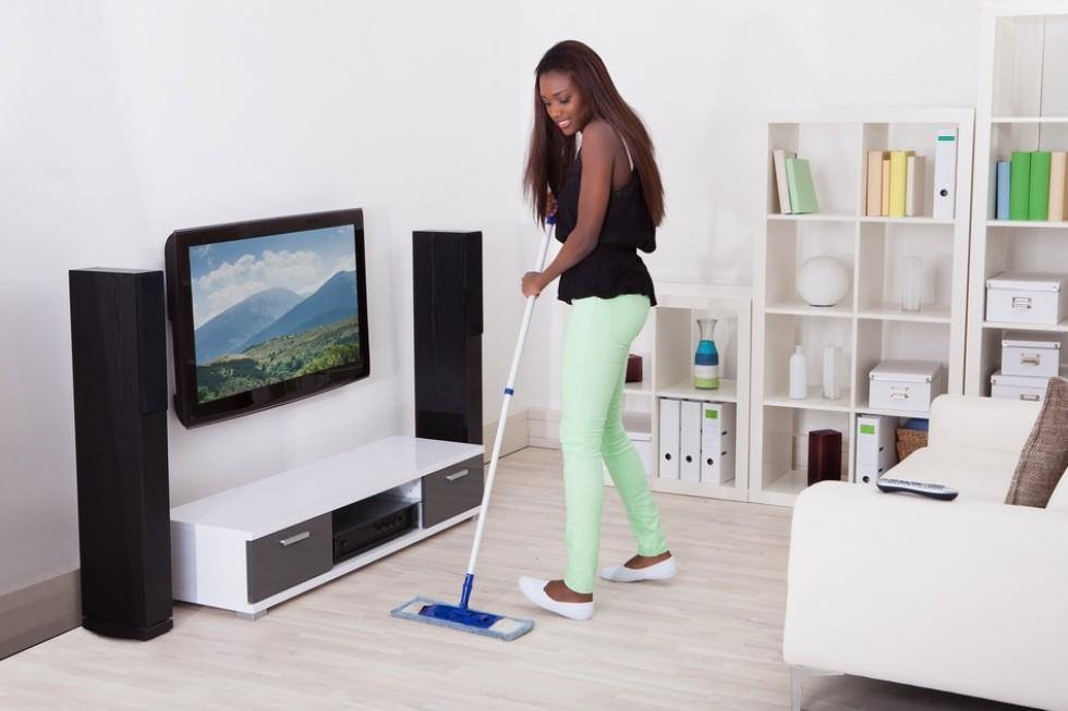 Woman Cleaning Floor In Living Room